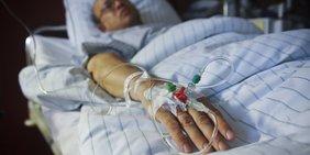 Mann liegt in Krankenhausbett mit Kathedern im Arm